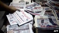 Un homme égyptien pointe le doigt sur une pile de journaux au Caire, le 4 juillet 2013.