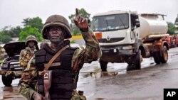 Binh sĩ Liberia tại 1 trạm kiểm soát được thiết lập để kiểm soát chặt chẽ những người định đến thủ đô từ những vùng nông thôn chịu ảnh hưởng nặng do vi rút Ebola, ở ngoại ô Monrovia, 7/8/2014.