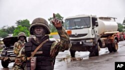 利比里亚军人在检查站叫停过路者,阻止疫区居民前往首都