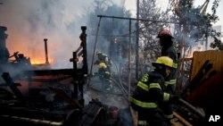 대규모 산불이 발생한 이스라엘 하이파에서 24일 소방관들이 주택가로 번진 불을 끄고 있다.