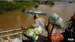 柬埔寨金邊郊區的代埃特村,一名小販和他的貨物乘小船渡過湄公河。 (2020年7月22日)