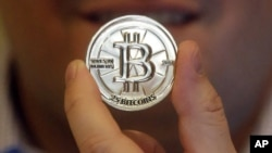 FILE - A man holds a token bearing the symbol of a cryptocurrency at his shop in Sandy, Utah. The tiny Marshall Islands is creating its own digital cryptocurrency in order to raise hard cash to pay bills and boost the economy.