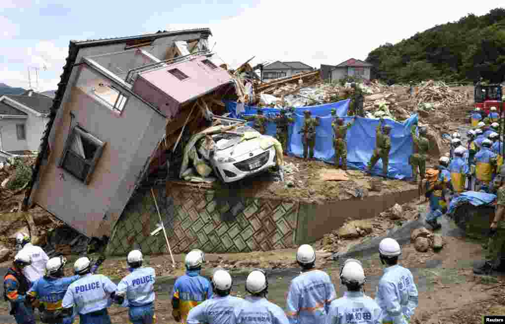 Rescue workers look for missing people in a house damaged by heavy rain in Kumano town, Hiroshima Prefecture, Japan, in this photo taken by Kyodo.