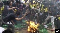 Những người Tây Tạng lưu vong cố gắng dập tắt lửa trên người của Jamphel Yeshi, thành niên 27 tuổi tự thiêu để phẩn đối trước chuyến đến thăm Ấn Độ của Chủ tịch Trung Quốc