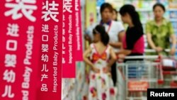 Customers talk to a sales assistant as they shop for milk powder in front of shelves displaying imported baby products at a supermarket in Beijing, August 5, 2013.