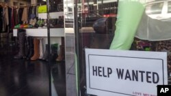 A help wanted sign is posted on the front window of a clothing boutique in Los Angeles, December 7, 2012.