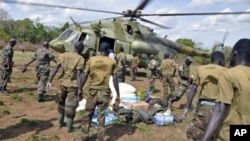 Ugandan soldiers, who are tracking down Lord's Resistance Army (LRA) fugitive leaders, load supplies from a military helicopter in a forest bordering Central African Republic, South Sudan and Democratic Republic of Congo, near river Chinko, April 18, 2012.