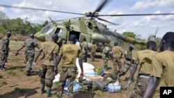 Ugandan soldiers, who are tracking down Lord's Resistance Army (LRA) fugitive leaders, load supplies off a military helicopter in a forest bordering Central African Republic, South Sudan and Democratic Republic of Congo, near river Chinko, April 18, 2012.
