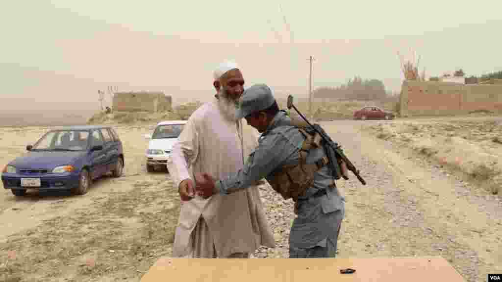 یک سرباز افغان در حال تلاشی مردم برای تامین بهتر امنیت