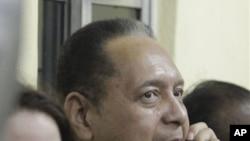 """Dikteta wa zamani wa Haiti Jean-Claude """"Baby Doc"""" Duvalier akizungumza kwa simu akiwa karibu na mkewe Veronique Roy walipowasili Port-au-Prince, Haiti, Jumapili, Jan. 16, 2011."""