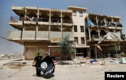 A member of the Iraqi security forces holds an Islamic State flag, after pulling it down from a building, in Fallujah, Iraq, June 25, 2016.