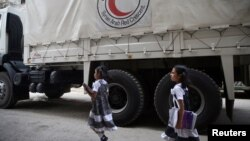 FILE - Girls walk near a Red Crescent aid convoy carrying urgent medical supplies in the rebel-held besieged town of Douma, near in Damascus, Syria, May 26, 2016.