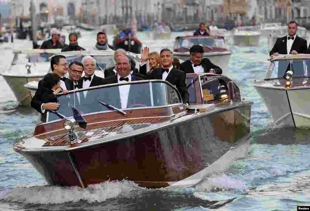 George Clooney gestures as travels on a taxi boat to the venue of a gala dinner ahead of his official wedding ceremony in Venice, Sept. 27, 2014.