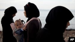 A woman refugee holds her child after arriving with others on a dinghy from Turkey at Lesbos Island, Greece, Sept. 9, 2015.
