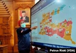Gubernur Jawa Timur Khofifah Indar Parawansa menunjukka peta persebaran virus corona di Jawa Timur. (Foto: VOA/Petrus Riski)
