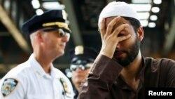 Učesnik protesta održanih zbog ubistva imama i njegovog pomoćnika u Njujorku