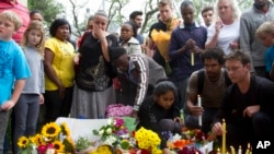 Mourners lay floral and candle tributes to former South African president Nelson Mandela outside his Johannesburg home, Dec. 6, 2013.