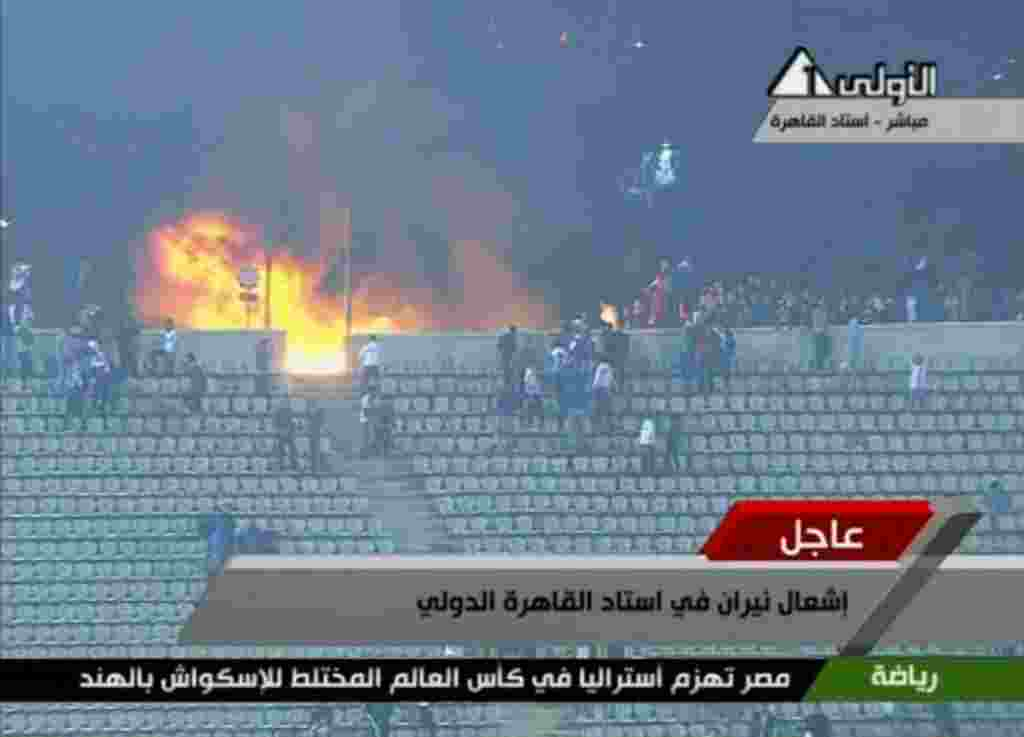 Gambar dari Egypt TV ini memperlihatkan kobaran api di salah satu sudut stadion sepakbola di Port Said, Mesir (1/2) (AP).