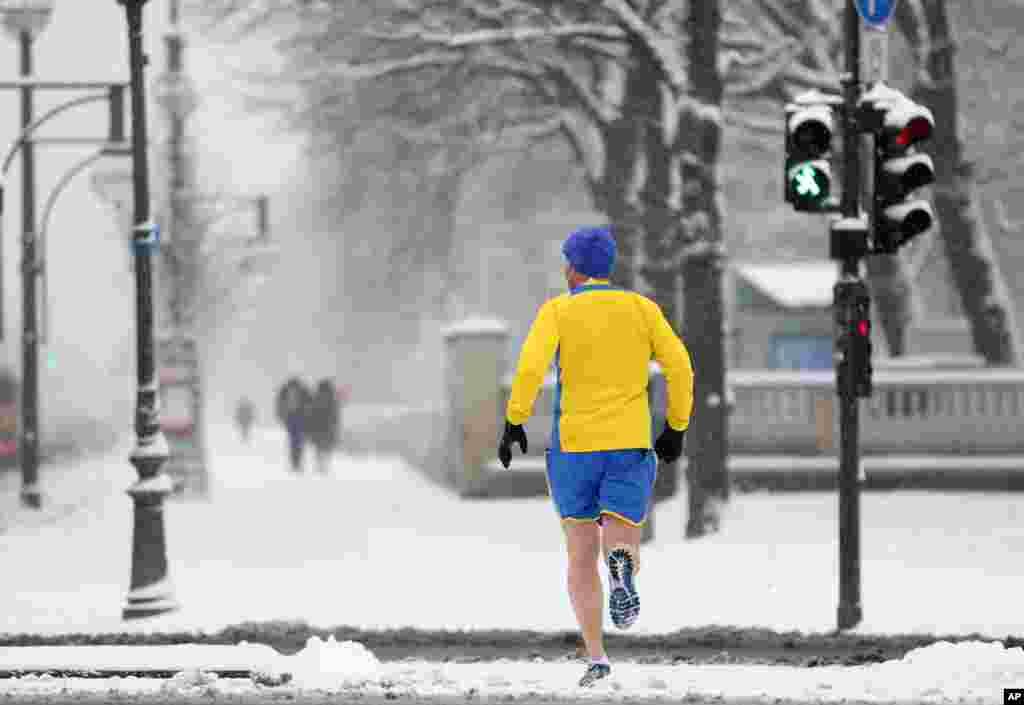 A jogger braves the cold temperatures and the snow in shorts in Berlin, Germany.