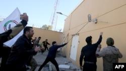 伊拉克示威者衝擊美國駐巴格達大使館的外牆,抗議者譴責美國對伊拉克境內伊朗支持的民兵發動空襲。2019年12月31日,法新社照片)