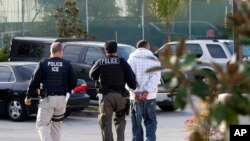 Immigration and Customs Enforcement agents take a suspect into custody as part of a nationwide immigration sweep in Chula Vista, California, March 30, 2012.