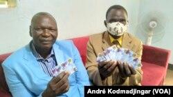 Dividi Boubar (à g.) et Natoïallah Ringar brandissent les doubles des cartes d'électeurs, à N'Djamena, au Tchad, le 7 avril 2021.