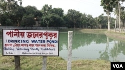 """Water from this pond is used to feed the Sulabh Water plant at Madhusudankati village. """"Bathing and washing of clothing are not allowed in this pond,"""" warns a signboard by the pond. (M. Hussain/VOA)"""