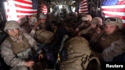 FILE - U.S. Marines are seen on board a helicopter at Kandahar air base upon the end of operations for the Marines and British combat troops in Helmand province, Oct. 27, 2014.