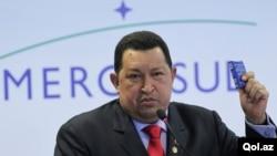 El presidente de Venezuela, Hugo Chávez, enseña una copia de su constitución venezolana al dirigirse a la prensa durante la Cumbre Extraordinaria de Mercosur que se realiza en Brasil.