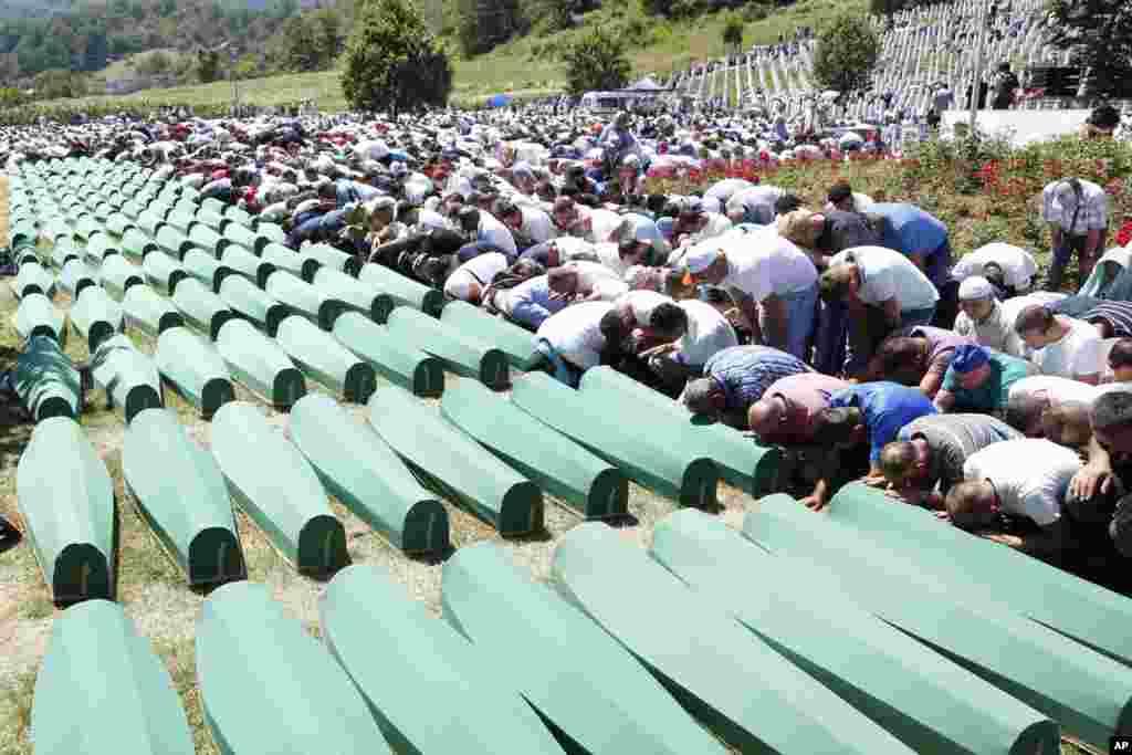 Người Bosnia cầu nguyện trước những quan tài trong tang lễ dành cho cho 127 nạn nhân tại khu Tưởng niệm Potocari gần Srebrenica, 150 kilômét về phía đông bắc thủ đô Sarajevo, Bosnia và Herzegovina.
