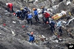 Rescue workers work on debris of the Germanwings jet at the crash site near Seyne-les-Alpes, France, March 26, 2015.
