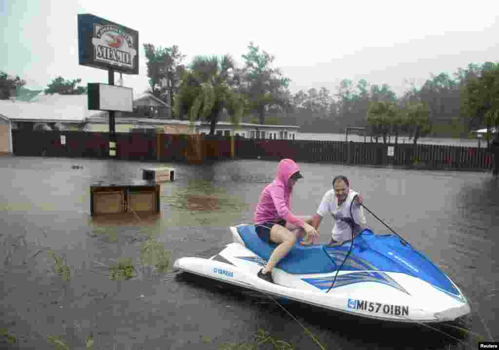 Owners Hank and Lori Plauche use a jet-ski to survey the damage to the Jourdan River Steamer, Seafood Restaurant as Hurricane Isaac passes through Kiln, Mississippi, August 29, 2012.