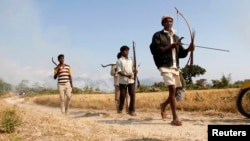 Tribal plantation workers armed with tools for self-defence move to a safer place after ethnic clashes in Tenganala village in Sonitpur district, in the northeastern Indian state of Assam, December 24, 2014.