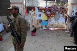 FILE - A soldier stands near a woman reading messages left by people for the victims of the Taliban attack on a school, in Peshawar, Pakistan, Dec. 23, 2014.