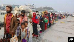 FILE - Rohingya refugees headed to the Bhasan Char island prepare to board navy vessels from the south eastern port city of Chattogram, Bangladesh.