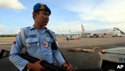 Seorang personel angkatan udara berjaga-jaga dekat pesawat Virgin Australia di Bali, Indonesia (25/4). (AP/Firdia Lisnawati)