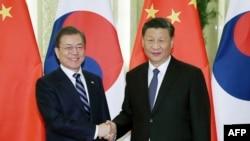 លោកប្រធានាធិបតី Moon Jae-in (រូបឆ្វេង) ចាប់ដៃជាមួយនឹងលោកប្រធានាធិបតី Xi Jinping មុនកិច្ចប្រជុំមួយនៅក្នុងក្រុងប៉េកាំង កាលពីថ្ងៃទី២៣ ខែធ្នូ ឆ្នាំ២០១៩។