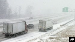 Truk melintasi jalan tol di North Ridgeville, negara bagian Ohio (26/12) di tengah badai salju. (AP/Mark Duncan)