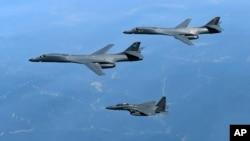 En esta foto de archive del 20 de junio de 2017 se ven dos bombarderos estadounidenses B-1B (arriba) junto a un bombardero surcoreano F-15K sobre la península coreana.