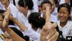 Cambodian students raise their hands while being addressed by U.N.-backed genocide tribunal officers at Bak Touk High School, in Phnom Penh.
