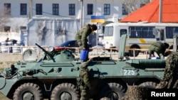 乌克兰军事基地前面疑似俄罗斯军人的武装人员及其装甲运兵车。乌克兰军队被俄军逼走