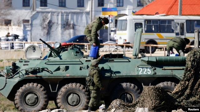 Armed men, believed to be Russian servicemen, supply an armored personnel carrier (APC) in front of a Ukrainian marine base in the Crimean port city of Feodosia March 23, 2014.