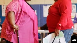 FILE - Two women converse in New York. New government figures released Friday, Oct. 13, 2017 showed small increases that were not considered statistically significant but were seen by some as a cause for concern. The adult obesity rate rose from to about