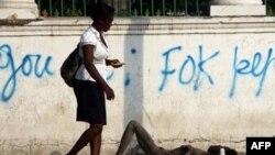 Phụ nữ Haiti đi ngang qua một người đàn ông bị dịch tả nằm bất tỉnh trên đường phố Port-au-Prince, ngày 17/11/2010