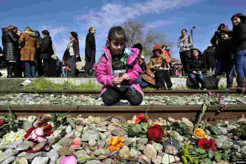 A girl places a flower on a railway track at the old train station of Thessaloniki during the 70th anniversary of the first deportation of Jews from Thessaloniki to Auschwitz, Thessaloniki, Greece.
