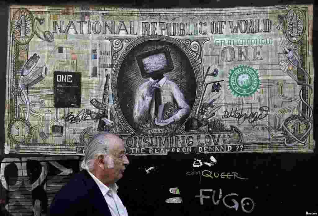 Seorang pria berjalan melewati graffiti yang mengilustrasikan uang kertas dollar yang dimodifikasi di Athena, Yunani.