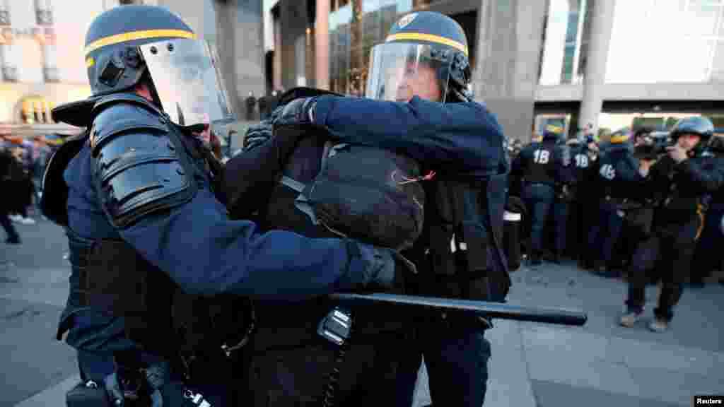Des CRS arrêtent des protestants dans les rues de Paris, le 23 avril 2017.