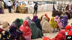 Internally displaced Somali women queue to receive food-aid rations at a distribution center