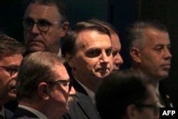 FILE - Brazil's President Jair Bolsonaro arrives at the inauguration ceremony of the new president of the Parliamentary Front of Agriculture (FPA), at the Clube Naval, in Brasilia, Jan. 19, 2019.