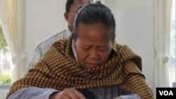 Seorang Ibu memberikan hak pilihnya di Birma.